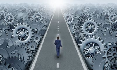 A business person walks down a road toward the horizon surrounded by working gears.