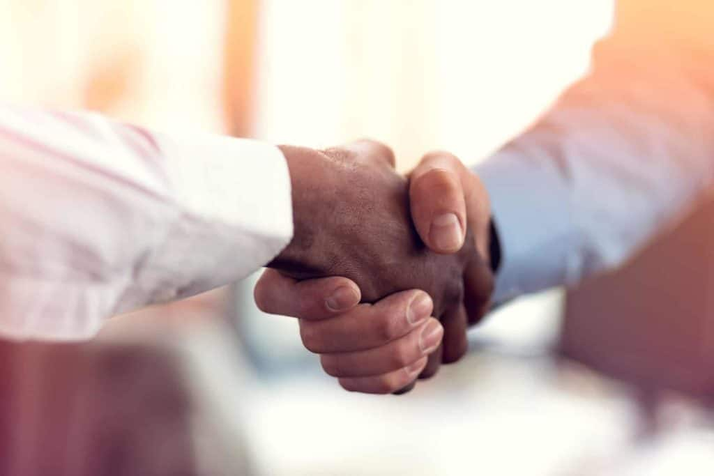 Employees of a business associate and a covered entity shake hands.