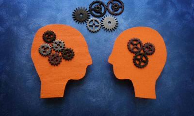 The profile of two heads connected by moving gears.
