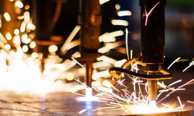Manufacturing equipment cutting metal with sparks.