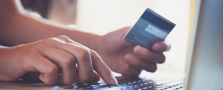 Person holds credit card while making a secure purchase online.