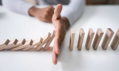 The hand of a business person blocks the domino effect.