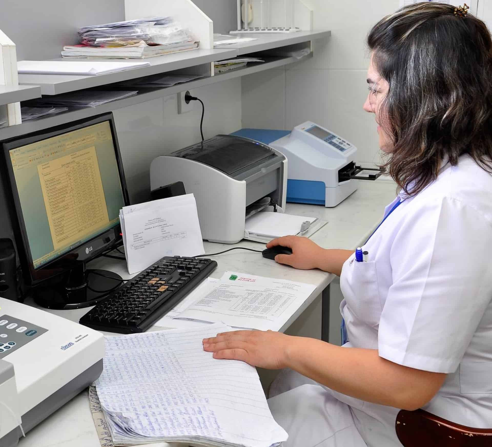 Doctor typing in protected health information at a computer in a medical facility.