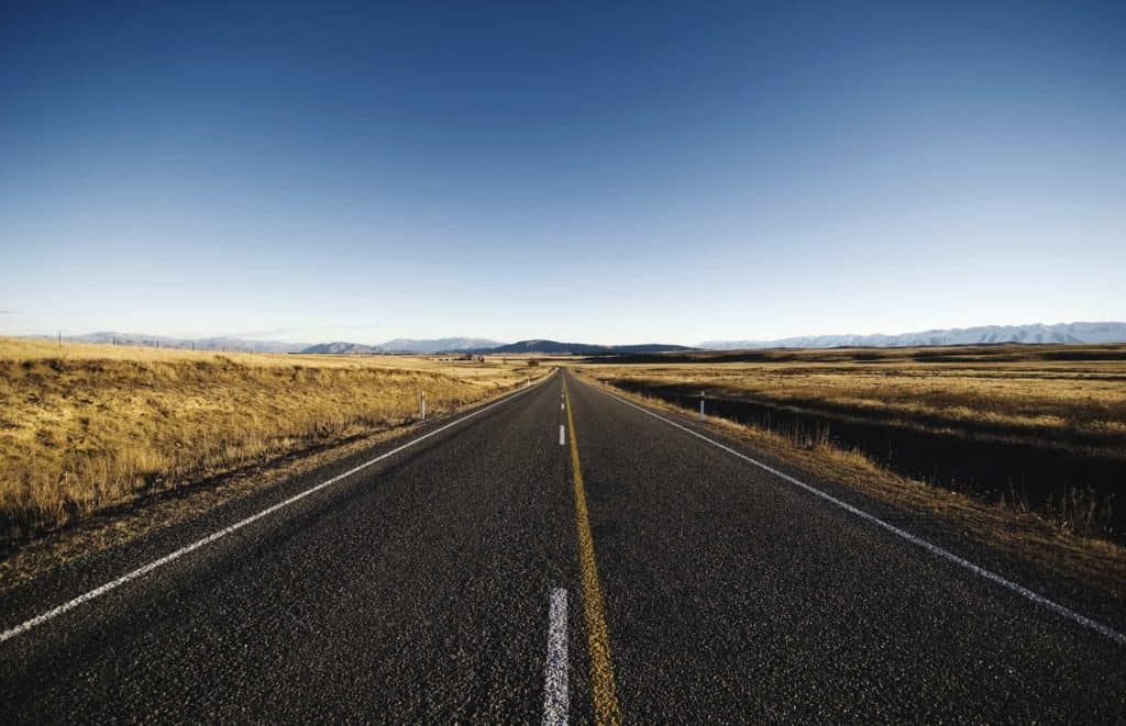 A highway stretches through an open field towards the horizon
