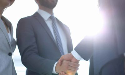 business leaders shake hands with the sun in the background