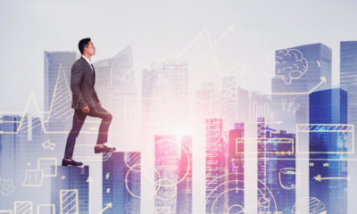 Young Asian businessman climbing bar chart in abstract city with double exposure of blurry business sketch. Concept of stock market and planning. Toned image